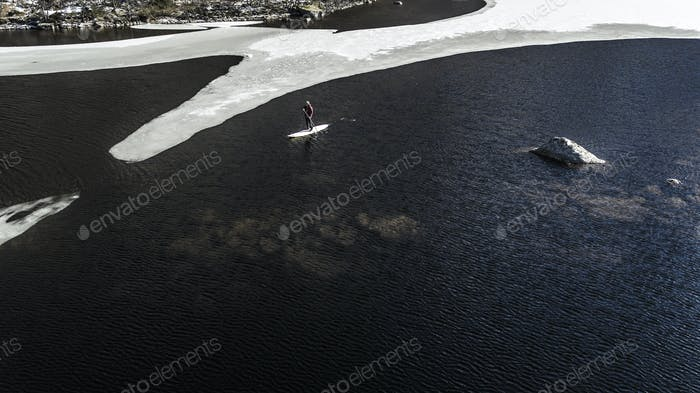 Aerial view of a paddleboarder on the water in an inlet with melting ice floes in the Lofoten