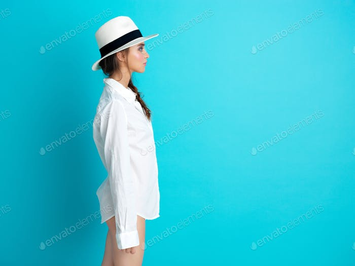 young woman blue background white hat, shirt