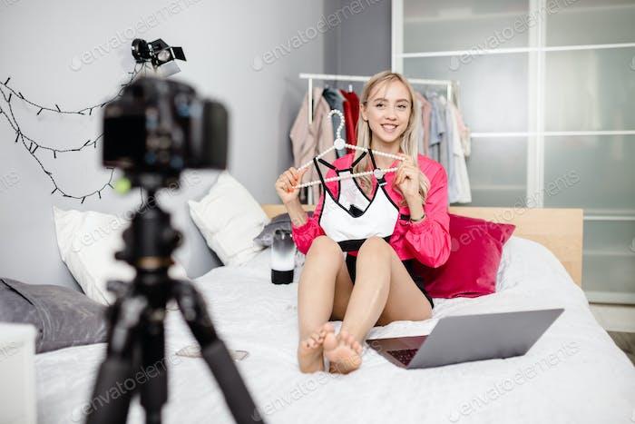 Junges Mädchen Bloggerin in hellen modischen Kleidern gekleidet wird für ihr Blog-Video gefilmt zeigt ein