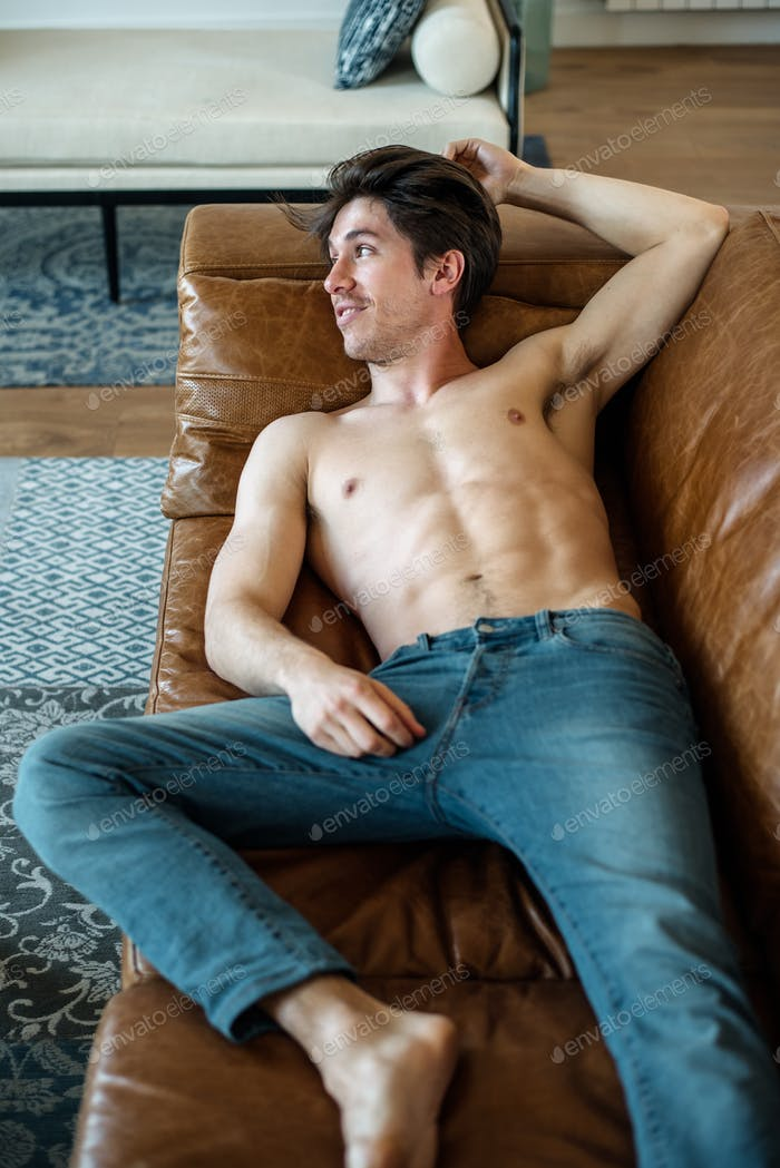 Happy man lying down on a couch