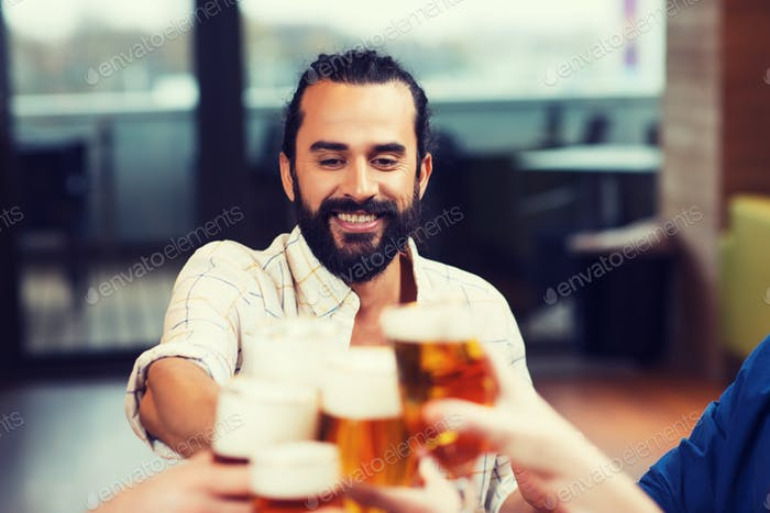 man clinking beer glass with friends at restaurant