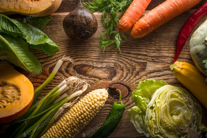 Carrots, Iceberg lettuce and various vegetables on a wooden table