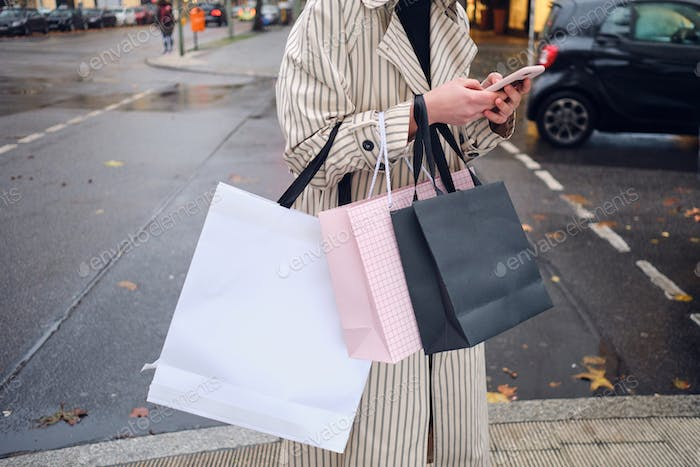 Close up stylish girl with shopping bags using smartphone on street