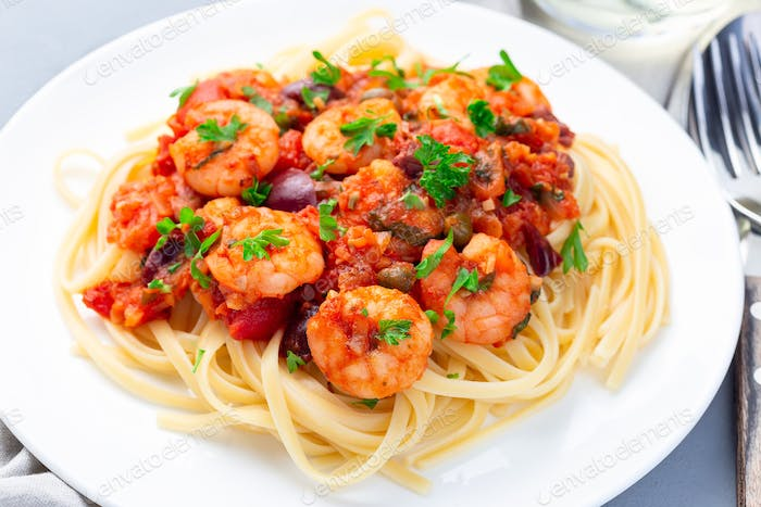 Italian dish shrimp linguine Puttanesca, pasta with shrimps in spicy tomato basil sauce, horizontal
