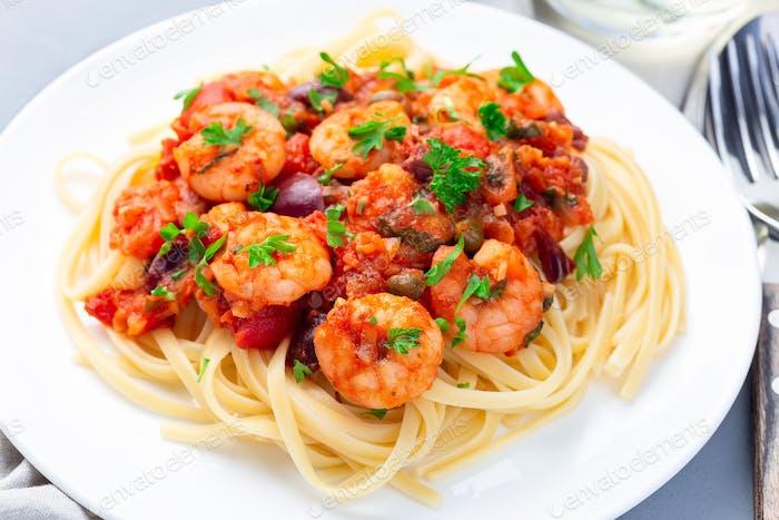 Italienisches Gericht Garnelen Linguine Puttanesca, Pasta mit Garnelen in würziger Tomaten-Basilikum-Sauce, horizontal