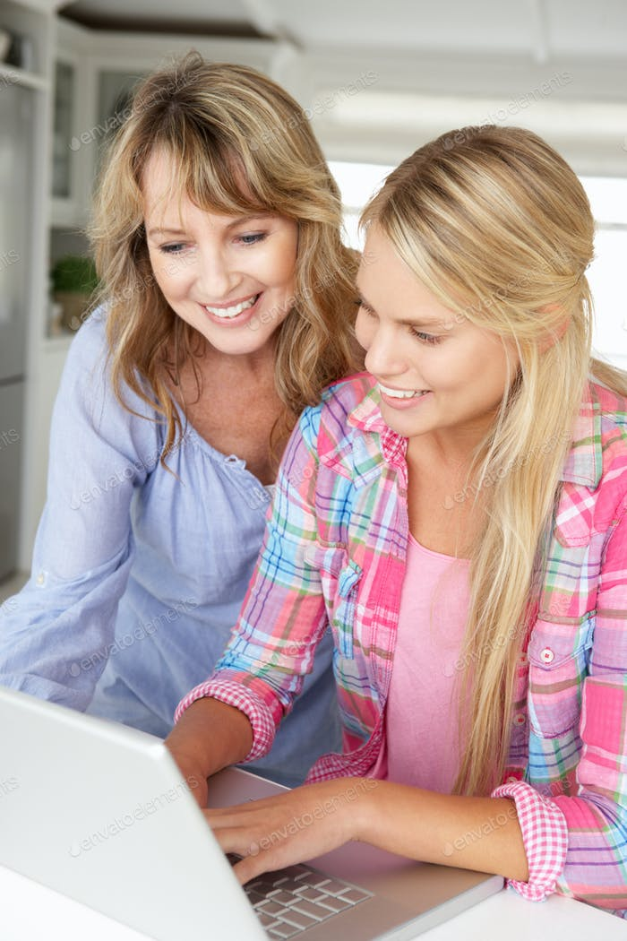 Mother and teenage daughter using laptop