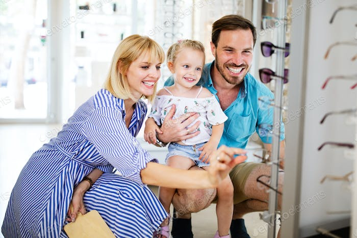 Happy mother and father choosing eyeglasses frame with their daughter in optical store