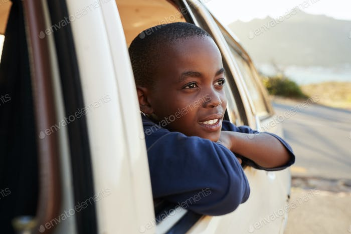 Boy Looking Out Of Car Window On Family Road Trip
