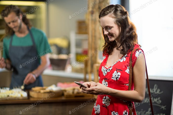 Smiling woman using mobile phone at counter