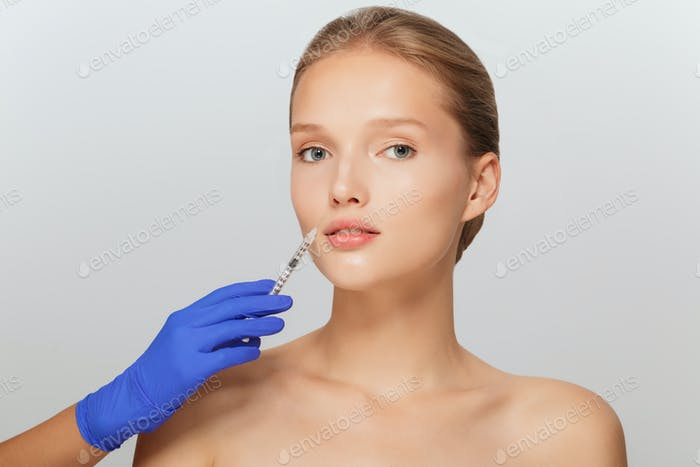 Portrait of young attractive lady getting beauty injection with