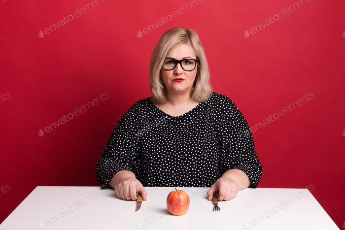 Portrait of a sad attractive overweight woman with an apple in studio.