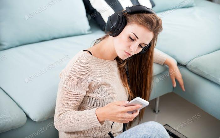 Женщина с наушниками слушает музыку дома