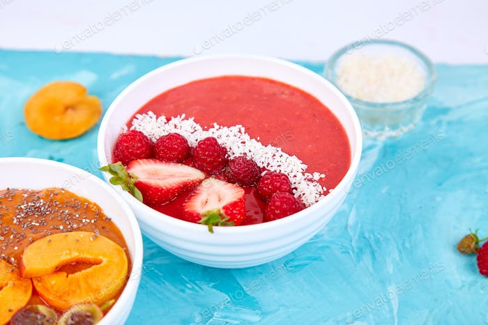 Smoothie bowls. Healthy breakfast bowl on blue background.