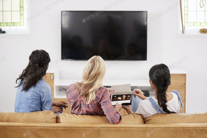 Female Friends Sitting On Sofa Watching Television Eating Candy