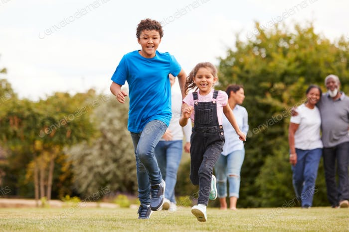 Children Running Ahead As Multi-Generation Mixed Race Family Walking In Garden At Home