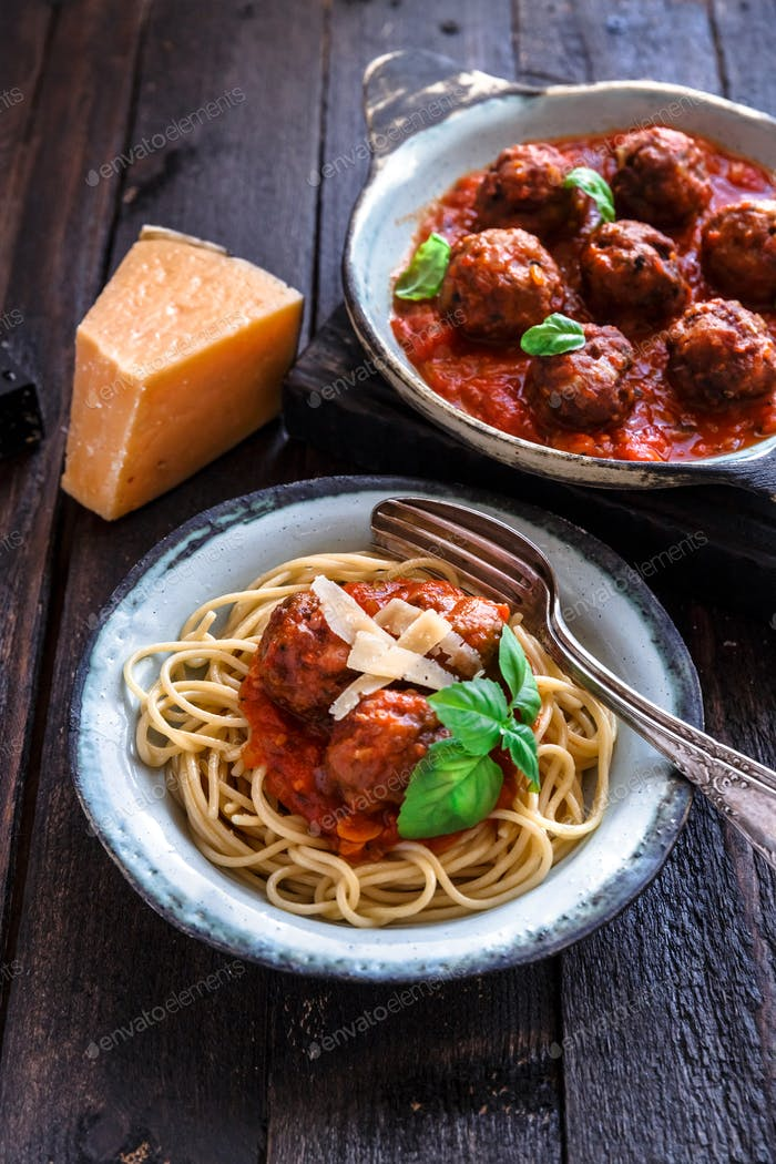 Spaghetti with meatballs and tomato sauce and basil, rustic style, selective focus