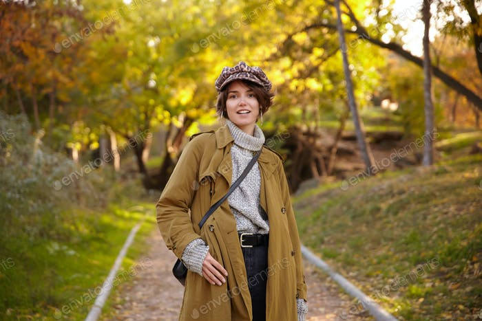 Fashionable young beautiful brown haired woman with bob hairstyle wearing trendy camel coat