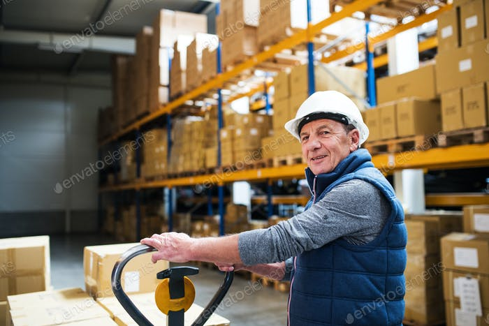 Senior male warehouse worker or a supervisor pulling a pallet truck with boxes.