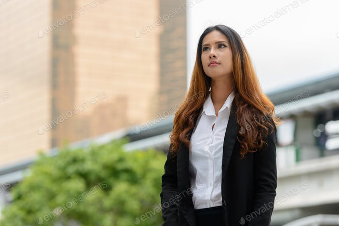 Young beautiful Asian businesswoman thinking in the city streets
