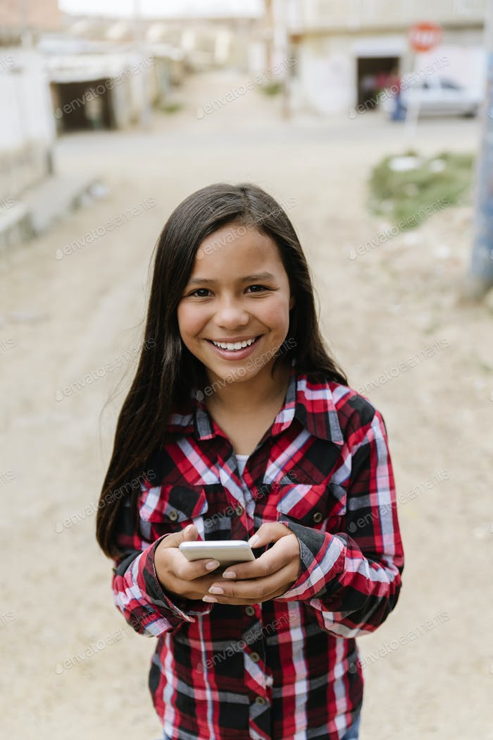 Portrait of cute latino girl using the mobile in shanty town.