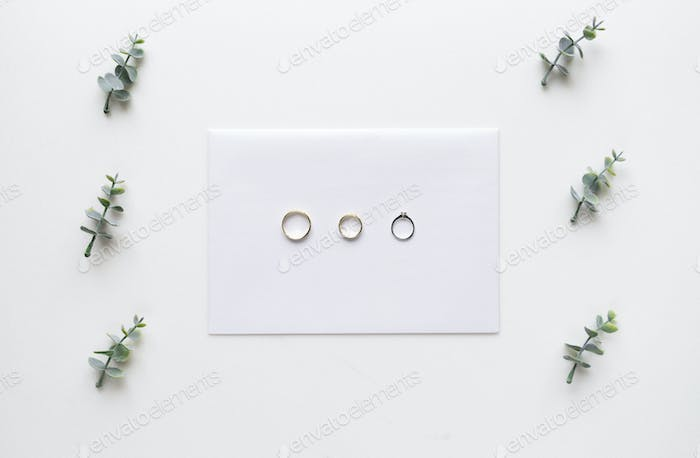 Wedding invitation card on white marble with wedding rings and o