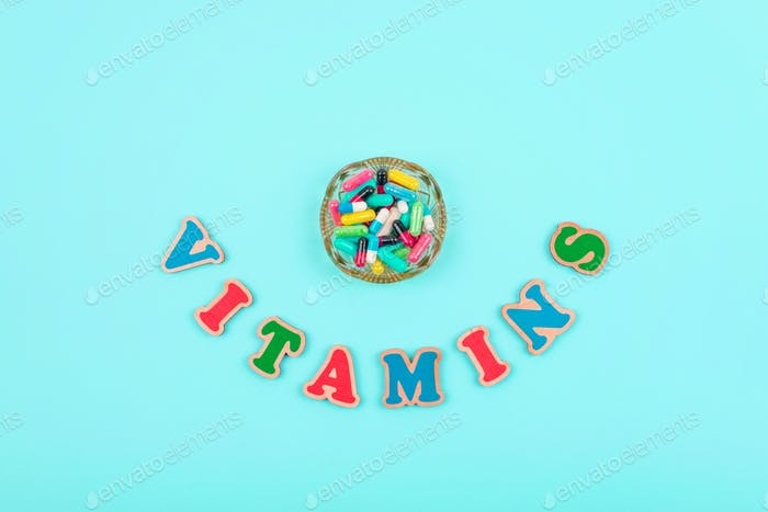 Different colorful pills and capsules in round plate and multicolored word VITAMINS on blue