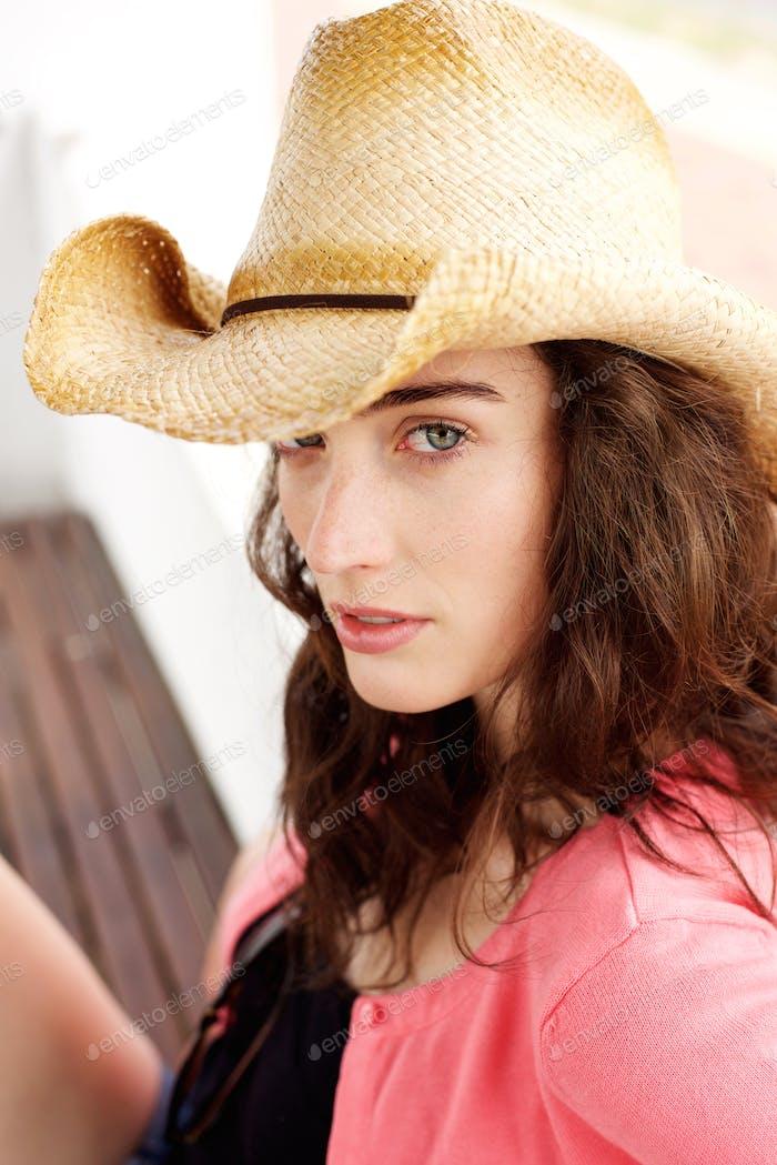 Ernste junge Dame sitzen außerhalb tragen Hut