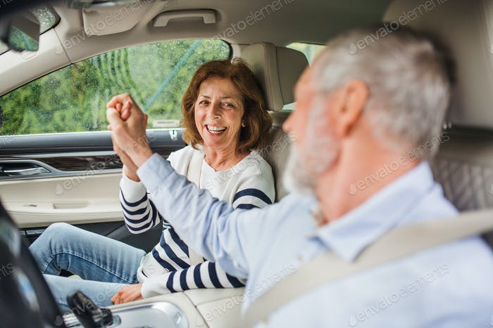 Happy senior couple with smartphone sitting in car, talking
