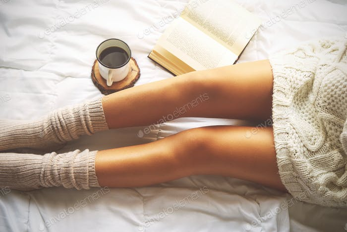 Soft photo of woman on the bed with book and cup of coffee, top