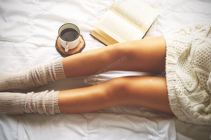Weiche Foto von Frau auf dem Bett mit Buch und Tasse Kaffee, top