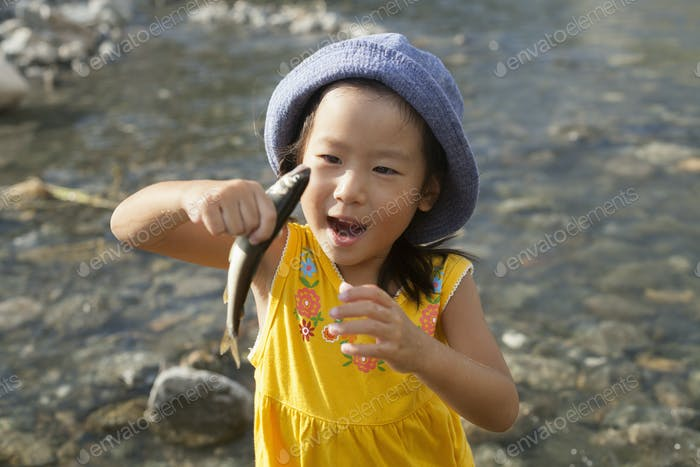 Young girl wearing a summer hat, holding a fish.