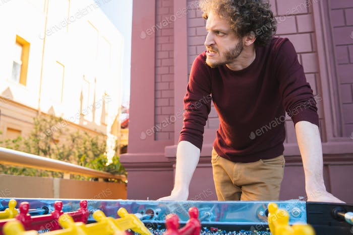 Young man playing table football.