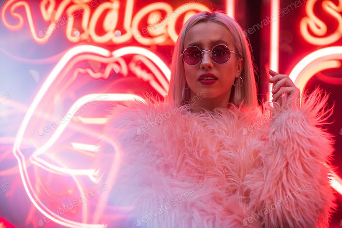 Cinematic portrait of blond girl with furry pink coat on neon si