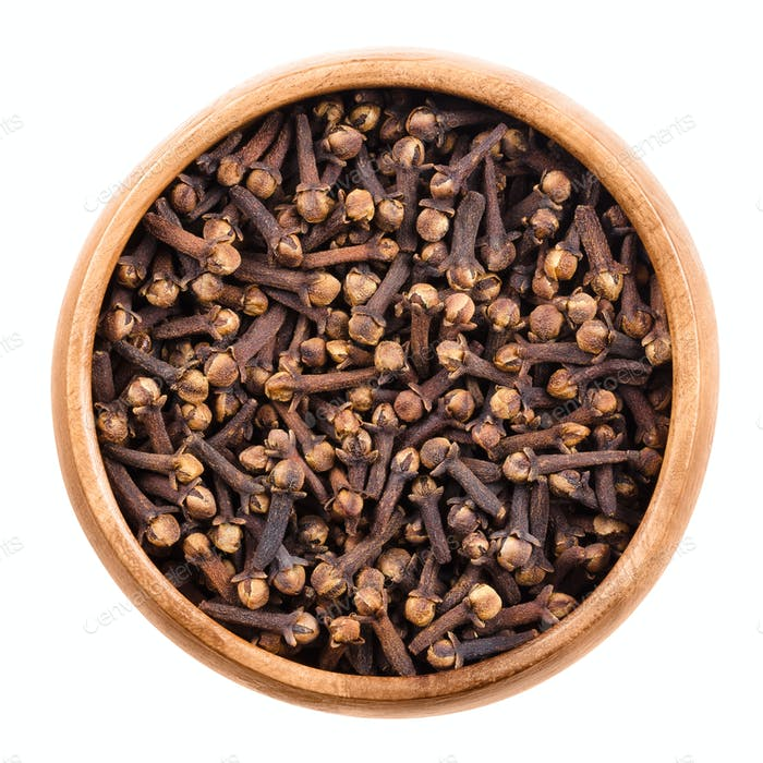 Dried cloves in a wooden bowl over white