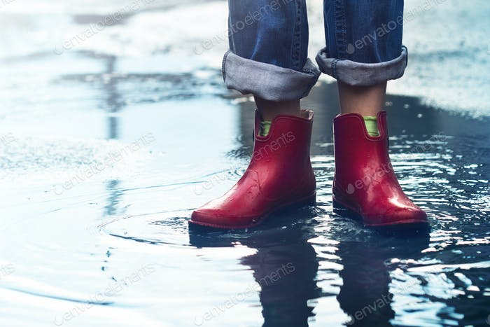 woman with red short boots standing in a puddle of rain water