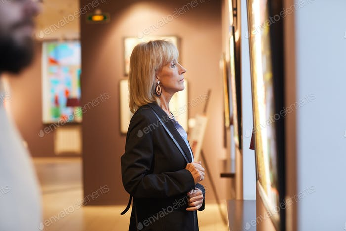 People Looking at Paintings in Art Gallery