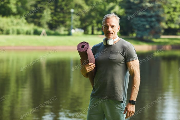 Muscular man with exercise mat