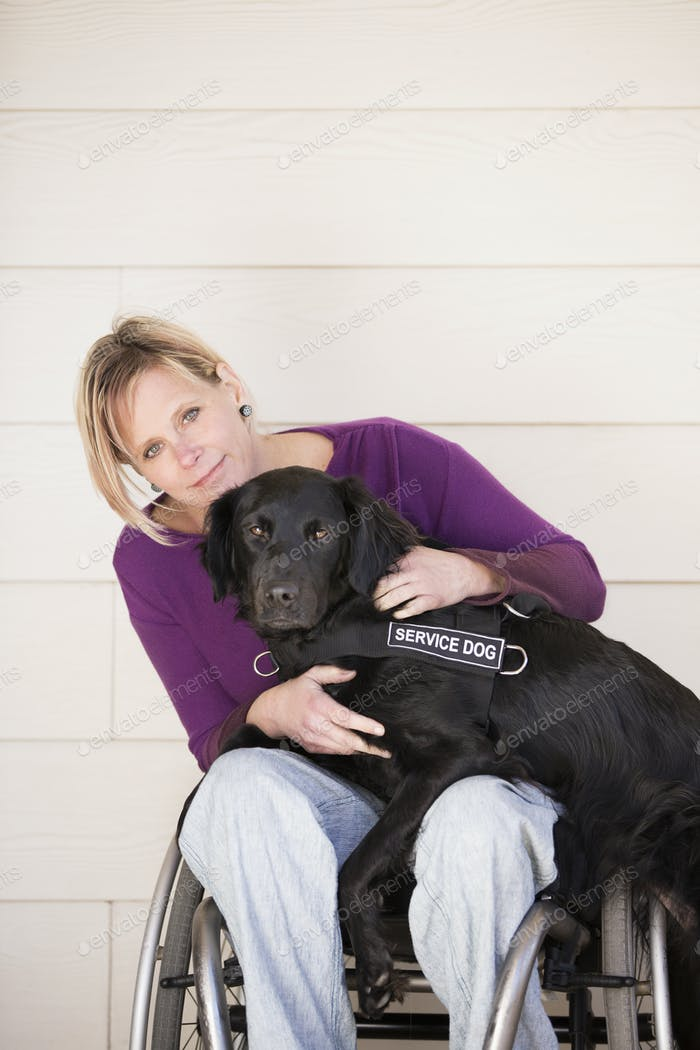 A mature woman wheelchair user with her arms around her service dog, a black labrador whose front