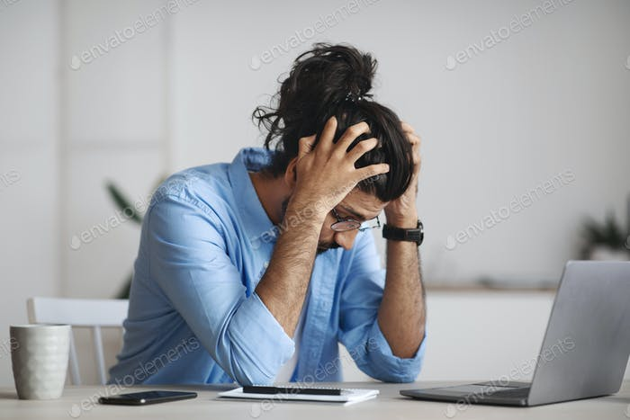 Work Problems. Desperate indian manager sitting at desk in office, suffering from business failure