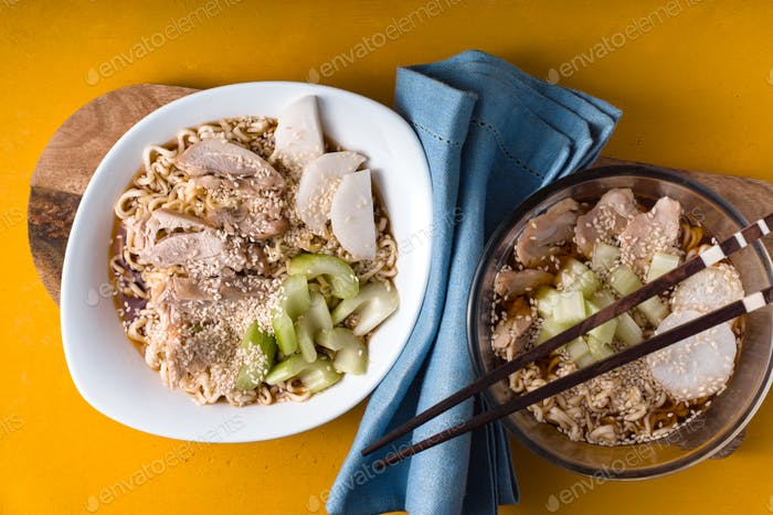 Two bowls of soup noodle ramen, celery, chicken on a yellow table