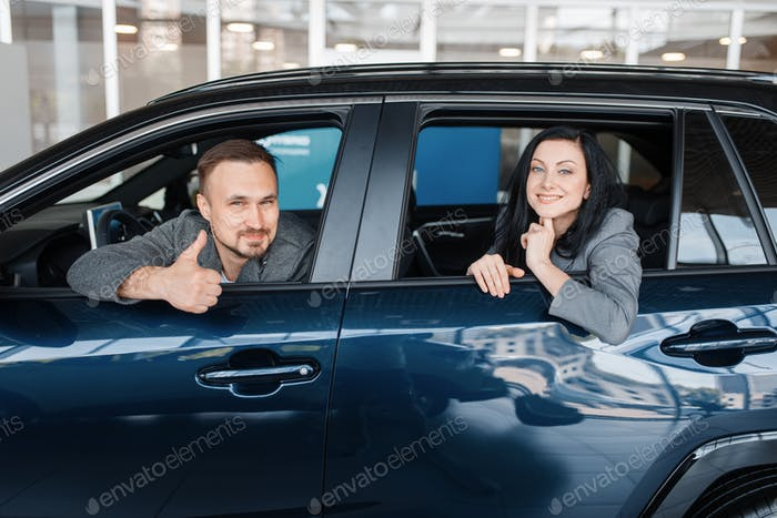 Happy couple sitting in new car, showroom