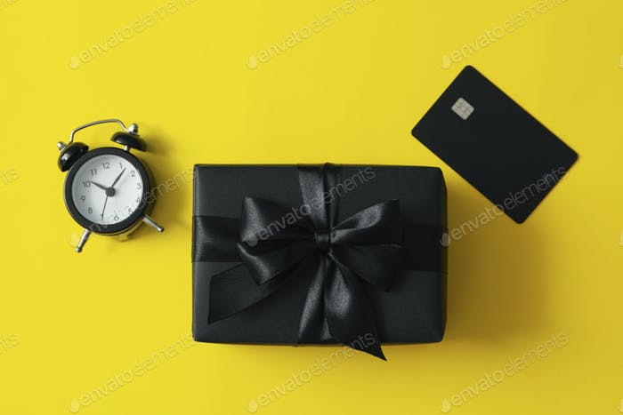 Gift box, alarm clock and card on yellow background
