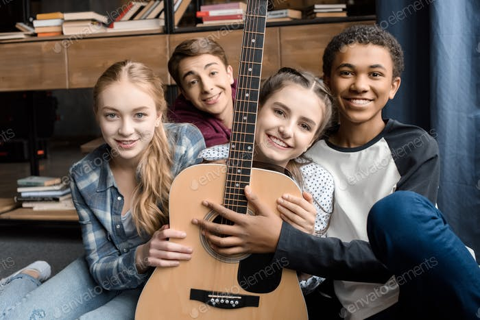 front view of happy teenagers holding guitar at home, teenagers playing guitar concept