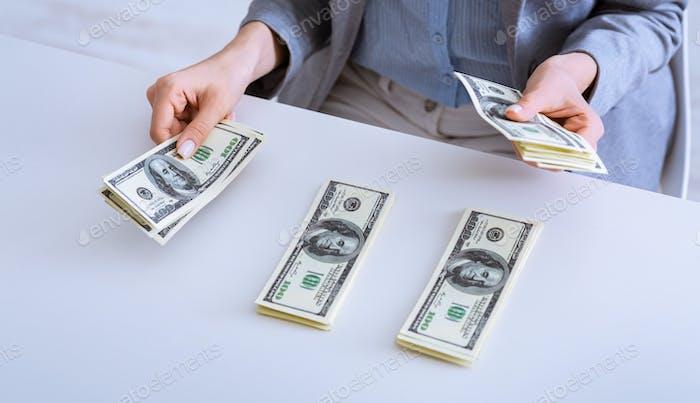 Verteilung der Mittel. Weibliche Hände legen Geld