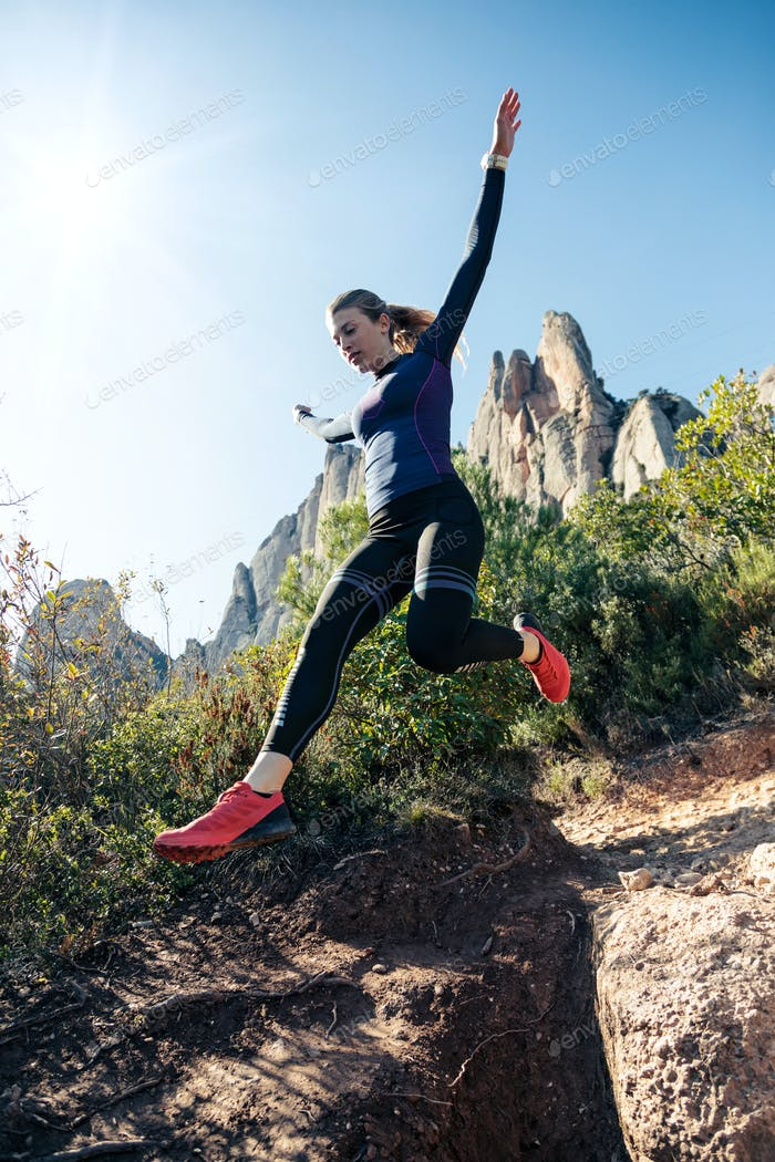 Young fitness woman trail runner running and jumping on rocky mo