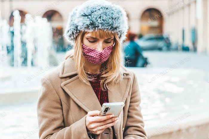 Young woman using mobile phone tracking Coronavirus spread