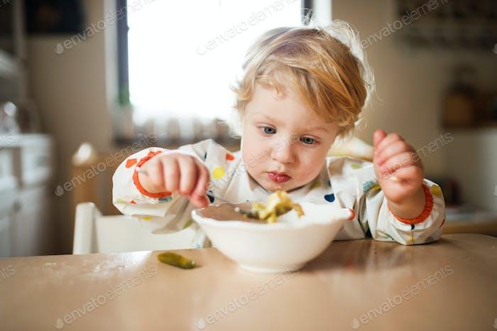 Ein Kleinkind, der zu Hause isst.