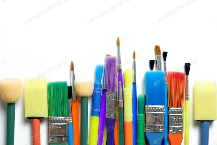 Row of artist paint brushes on white background