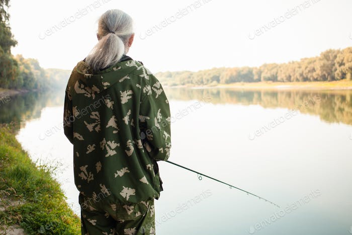 senior concept. pensioner fishes on the river in his spare time. A useful hobby, outdoor activities