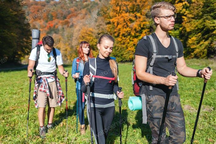 Amigos con mochilas caminando al aire libre juntos, trekking y turismo